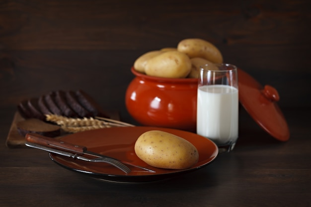 Fresh potatoes in a clay plate on a background of the dark wooden surface.