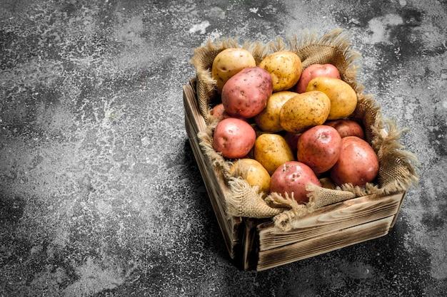 箱に入った新鮮なジャガイモ。素朴なテーブルの上。