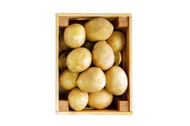 Свежий картофель в деревянном ящике на белом фоне. вид сверху.