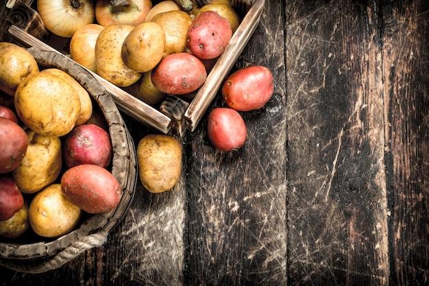 Свежий картофель в деревянном ящике. на деревянном фоне.