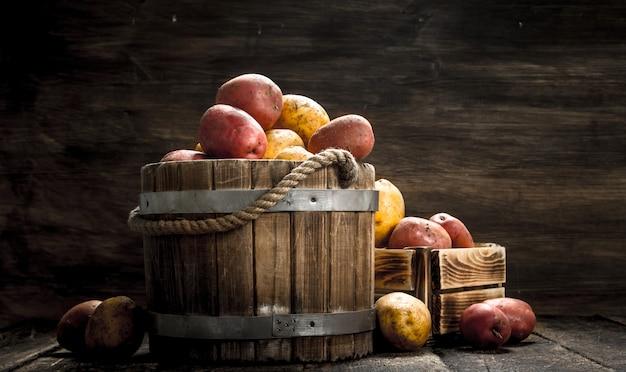 Свежий картофель в деревянном ведре. на деревянном фоне.