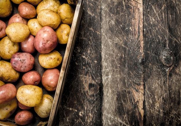 古い箱に入った新鮮なジャガイモ。木製のテーブルの上。