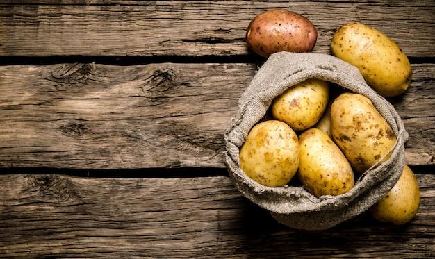 나무 배경에 오래 된 자루에 신선한 감자