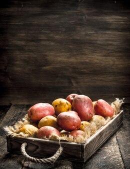 Свежий картофель в старом лотке. на деревянном фоне.