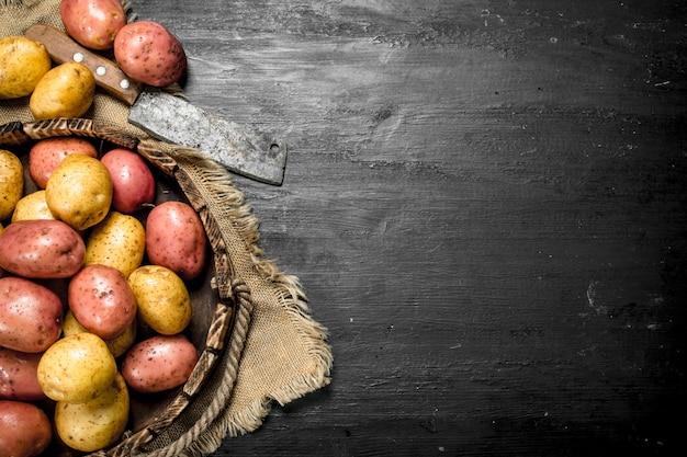 黒い黒板の古い木製トレイに新鮮なジャガイモ。