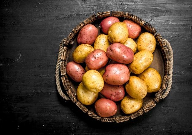 Свежий картофель в старом деревянном подносе