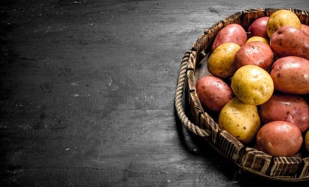 Свежий картофель в старом деревянном подносе.