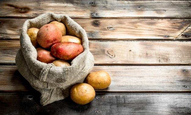 자루에 신선한 감자. 나무 배경