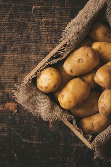 Свежий картофель на деревянном фоне