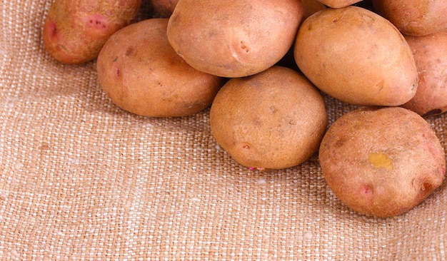 Свежий картофель на мешковине крупным планом