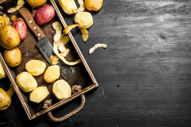 黒い黒板のトレイに新鮮なジャガイモ。