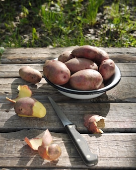 Fresh potatoes in a plate on a wooden table in nature