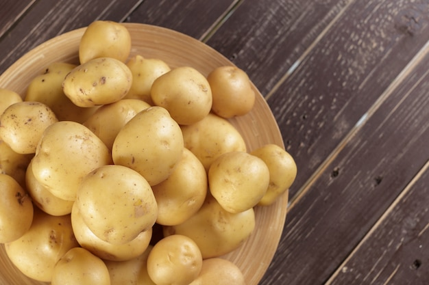 Fresh potatoes on the wood background