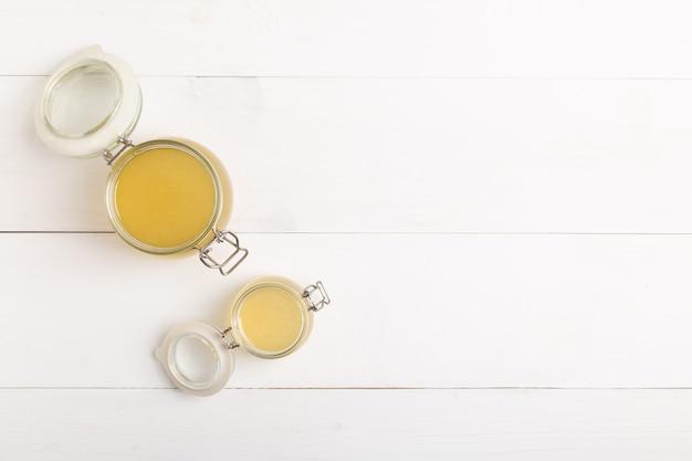 白いテーブルの上のガラスの瓶に新鮮な鶏肉のスープ。コピースペースのある上面図