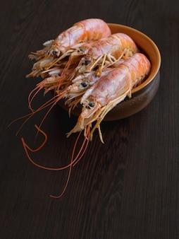 ボウルにキッチンテーブルの上に新鮮なエビ。調理した新鮮な海老