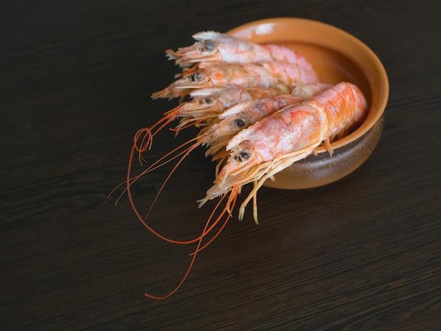 Свежие креветки на кухонном столе в миску. приготовленные свежие гигантские креветки