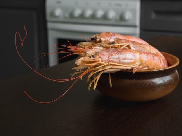 Свежие креветки на кухонном столе в миске