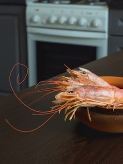 Свежие креветки на кухонном столе в миску.