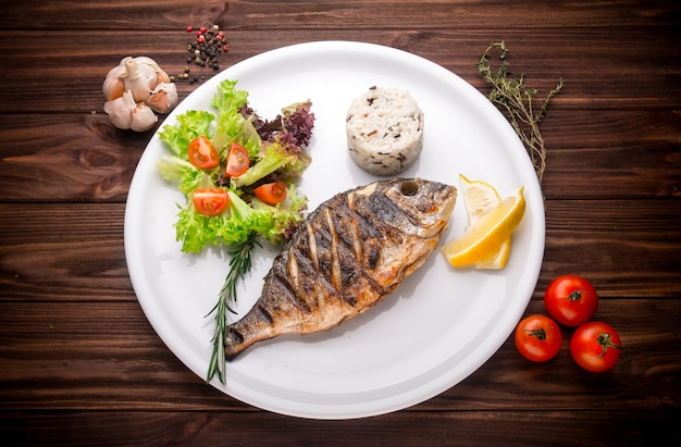 Fresh prepared dorado or sea bream fish with lemon, herbs on wooden background