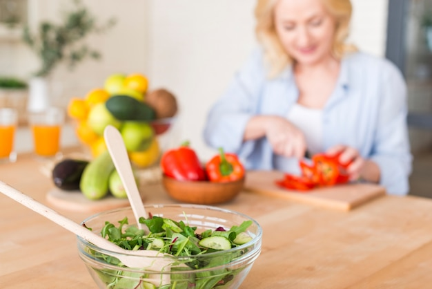 Fresh prepared salad in the glass bowl with wooden spoon and woman at background