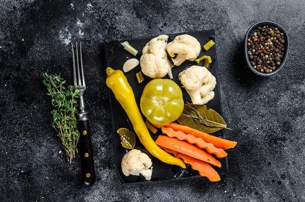 新鮮な野菜、自家製のおいしいピクルスを大理石のボードに保存します。黒の背景。上面図。