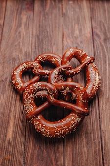 Fresh pretzel sprinkled with sesame seeds on a wooden table