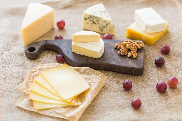 신선한 제품. 소박한 테이블에 치즈, 브리, 카망베르, 포도, 견과류.