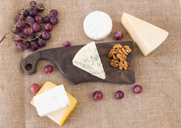 Fresh products. cheese, brie, camembert, grapes and nuts on rustic table.