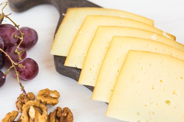신선한 제품. 시골 풍 테이블에 포도와 견과류와 치즈를 슬라이스.
