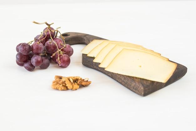 Свежие продукты. нарезанный сыр с виноградом и орехами на деревенском столе.