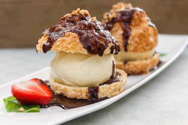 Fresh profiteroles with ice cream and chocolate on a white plate.