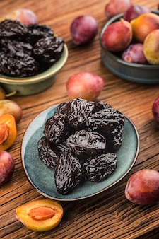 Fresh  prune and dried  prune on wooden board wall