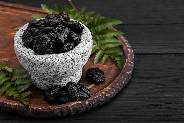 石のボウルに新鮮なプルーン。石の暗いテーブルのプルーン。健康食品を剪定します。ボウルに梅を乾燥させた。