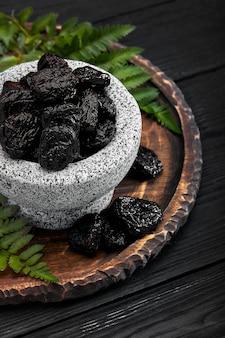 石のボウルに新鮮なプルーン。石の暗いテーブルのプルーン。健康食品を剪定します。ボウルにプルーン。
