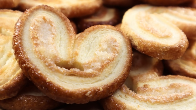 ハートの形をした新鮮なパイ生地のパームクッキー。古典的なフランスのペストリー。豚の耳、象の耳のクッキー、フランスの心。上からの眺め。