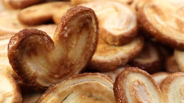 ハートの形をした新鮮なパイ生地のパームクッキー。古典的なフランスのペストリー。豚の耳、象の耳のクッキー、フランスの心。