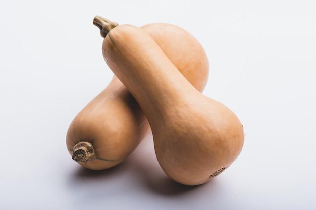 Свежая тыква, мускатный орех, сквош на белом фоне, органические сырые продукты для хорошего здоровья, растительный ингредиент
