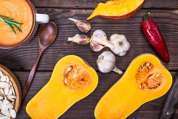 Fresh pumpkin cut in half and pumpkin soup