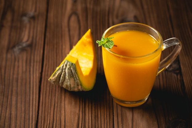 Fresh pumpkin juice in glass on wooden table.