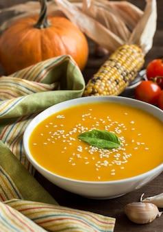 新鮮なカボチャのスープと茶色の木製のテーブルで野菜をクローズアップ
