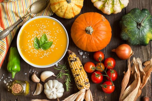 新鮮なカボチャのスープと野菜の木製テーブル