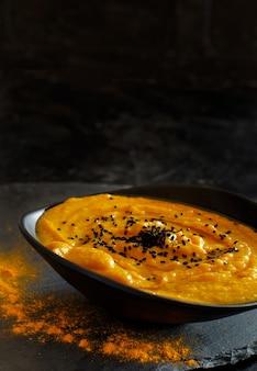 暗い背景のボウルに新鮮なカボチャのスープ