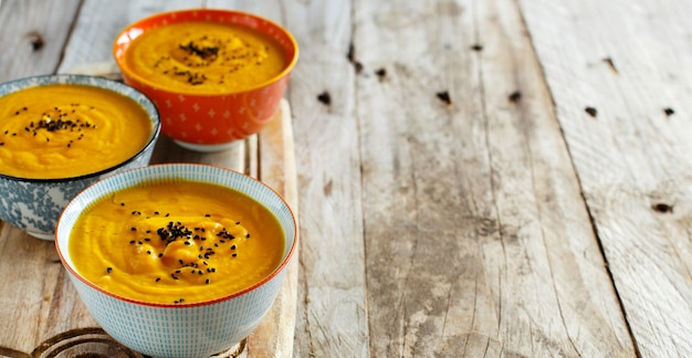 木製のテーブルの上の3つのボウルの新鮮なカボチャスープ