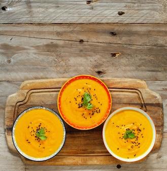 木製のテーブルの上の3つのボウルに新鮮なカボチャのスープ