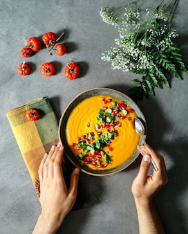 Fresh pumpkin soup topped with parsley and pomegranate seeds