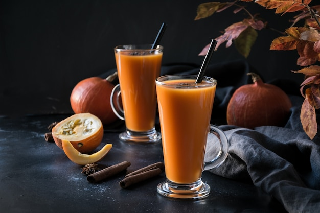 Fresh pumpkin spice smoothie or juice on dark. autumn, fall or winter hot drink on dark.