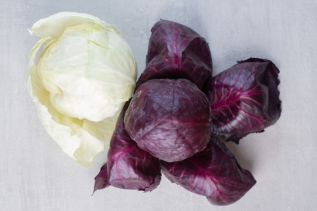 Свежие фиолетовые и белые капусты на каменной поверхности. фото высокого качества