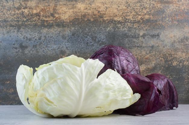 石のテーブルに新鮮な紫と白のキャベツ。高品質の写真