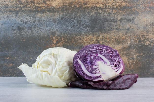 Свежие фиолетовые и белые капусты на каменном столе. фото высокого качества