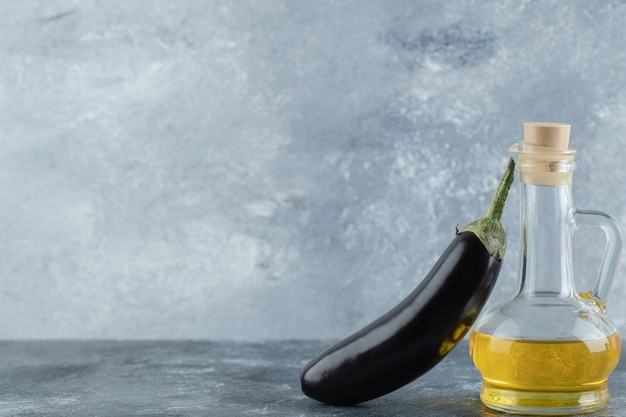 Fresh purple eggplant with oil on grey background.
